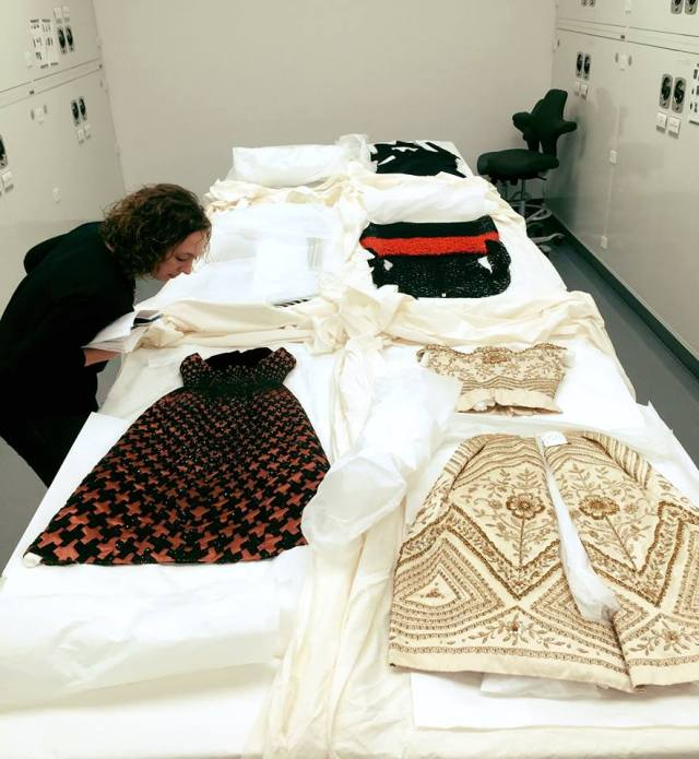 Arts Professional Lauren Bierly inspects exhibition items